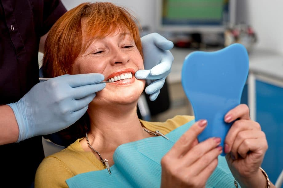 woman in dental chair holding mirror and looking at teeth