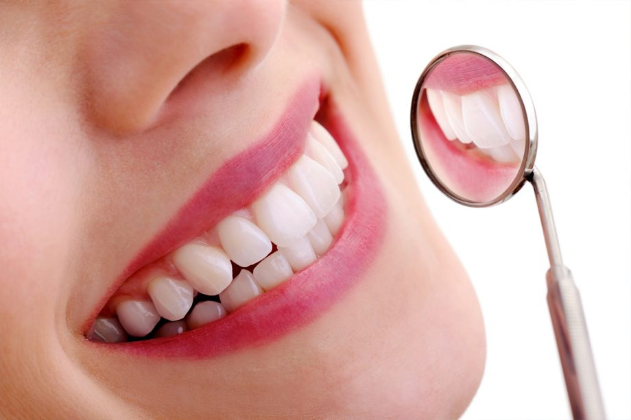 close up of young woman's smile and dental mirror