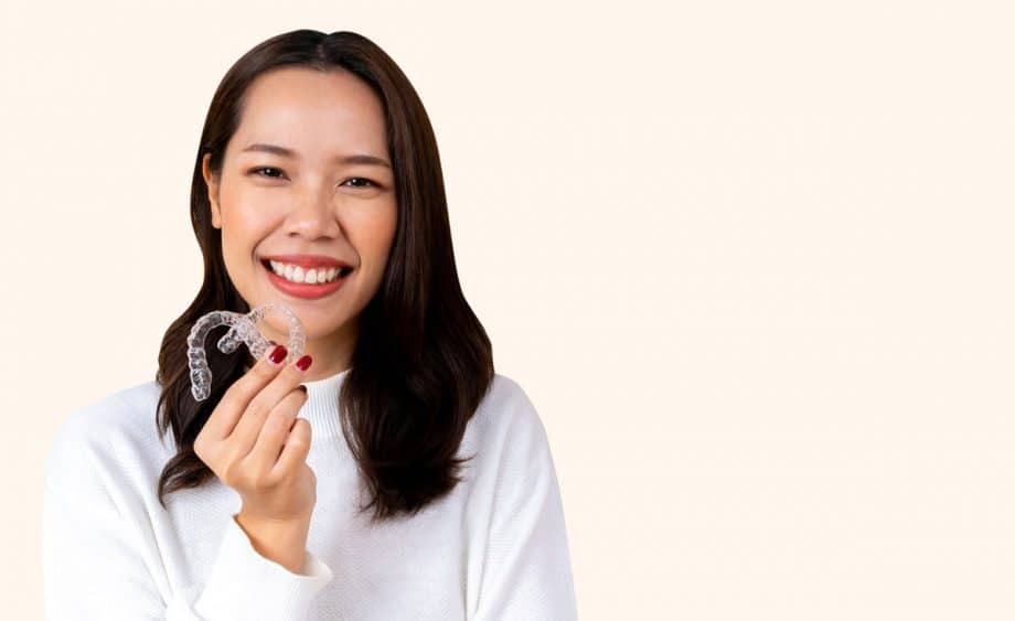 smiling woman holding Invisalign